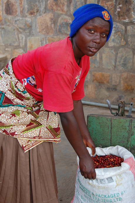 Juliene Njirantibankundiye weighs her bag of cherries after sorting out the ones with defects. It comes in at 20 kilos.
